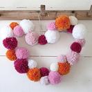 Corona decorativa con pompones de lana